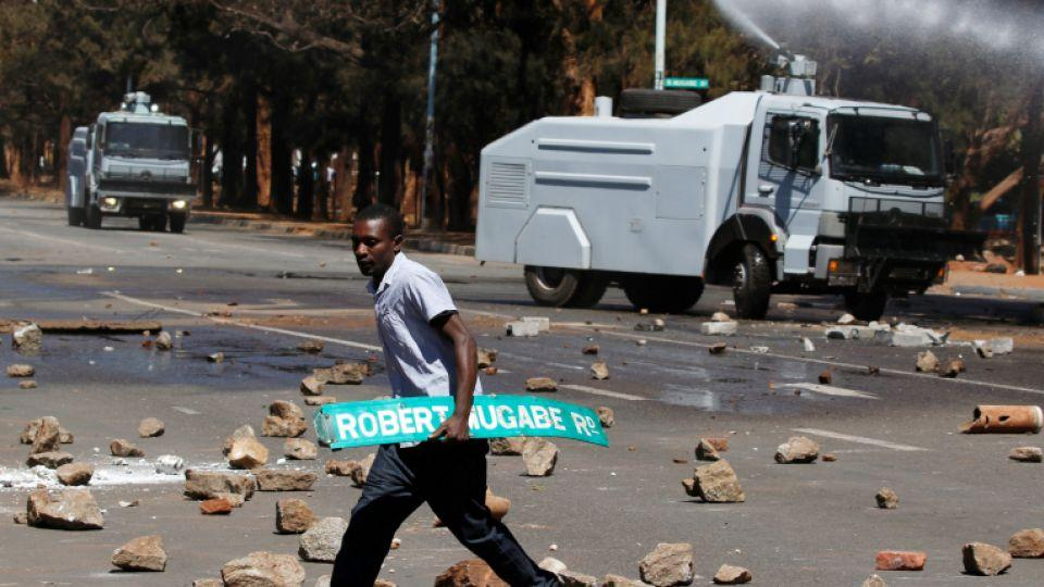 A man carries a street sign as opposition party supporters clash with police in Harare.