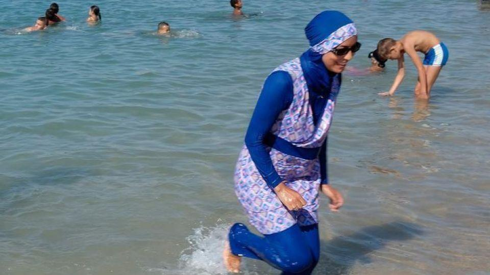 A woman wearing a burkini walks in the water August 27, 2016 on a beach in Marseille, France, the day after the country's highest administrative court suspended a ban on full-body burkini swimsuits. Image: Reuters.
