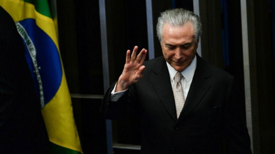 President Michel Temer waves as he takes office before the plenary of the Brazilian Senate in Brasilia, on August 31, 2016.