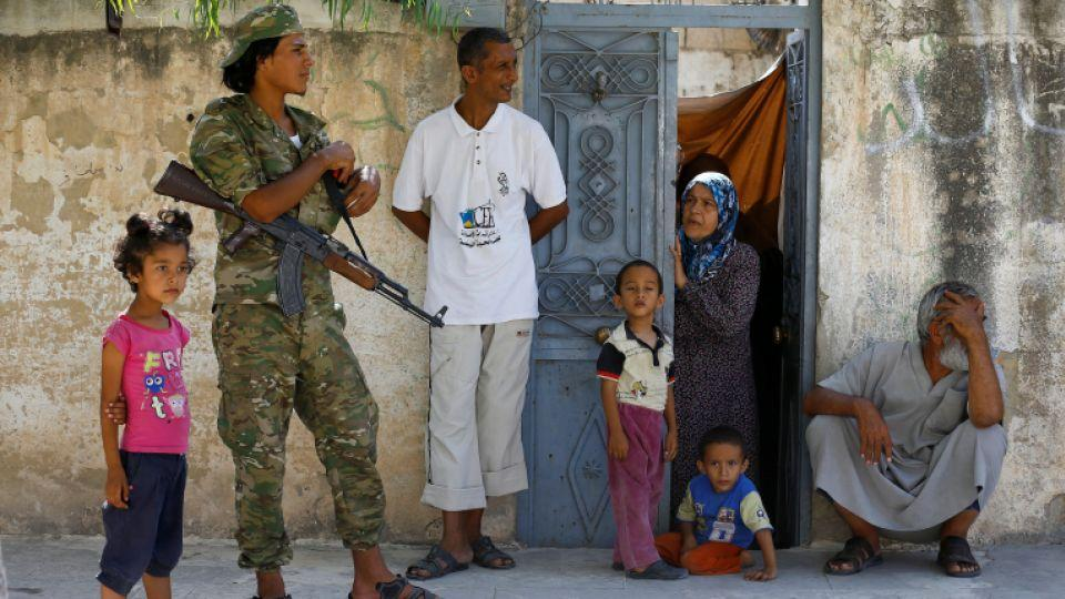 A member of the Turkish-backed Free Syrian Army (FSA) is seen with local people in the border town of Jarabulus, Syria, August 31, 2016.