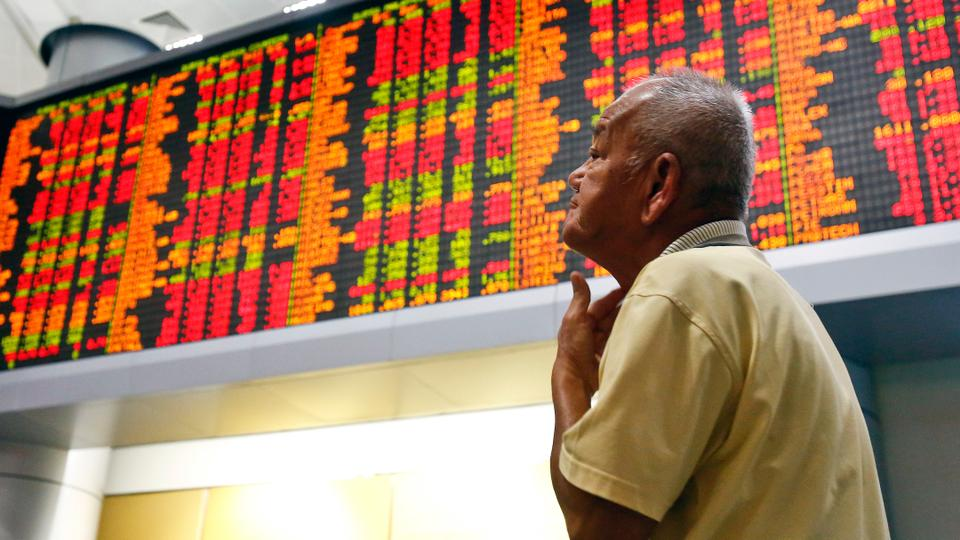 A man watches trading boards at a private stock market gallery in Kuala  Lumpur, Malaysia