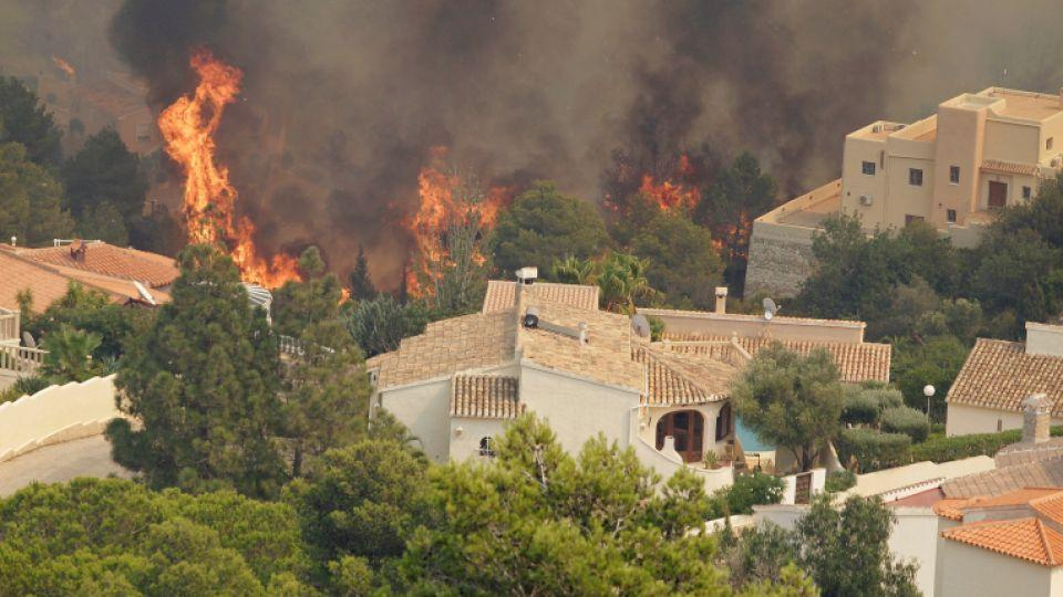 Trees burn next to houses during a wildfire in Benitatxell near Alicante, Spain September 5, 2016.