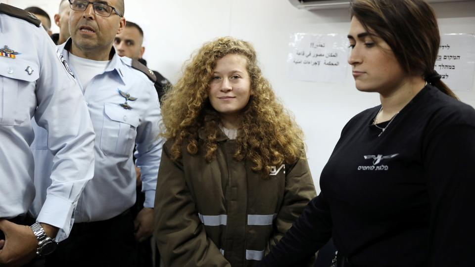 Palestinian teen Ahed Tamimi enters a military courtroom escorted by Israeli security personnel at Ofer Prison, near the West Bank city of Ramallah, January 15, 2018.