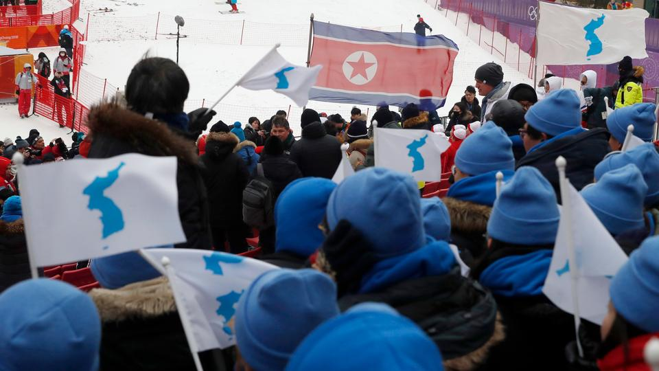 South Koreans cheering in favour of a unified Korea are seen with a North Korean flag in the background at Pyeongchang Winter Olympics in  Pyeongchang County, South Korea on February 14, 2018.