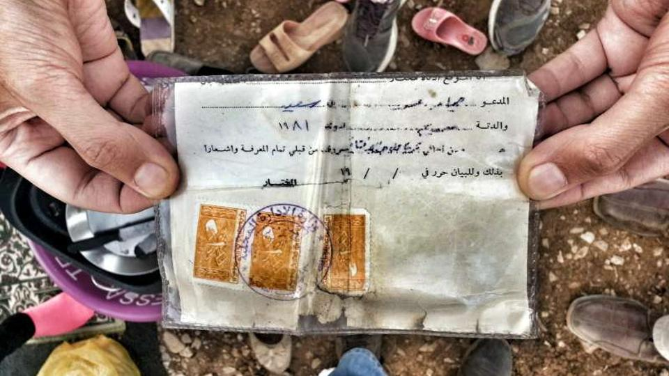 """A Syrian refugee shows UNHCR his """"maktoumeen"""" or or """"unregistered"""" card issued in Syria. This document, given to unregistered stateless Kurds, confers no rights or status."""