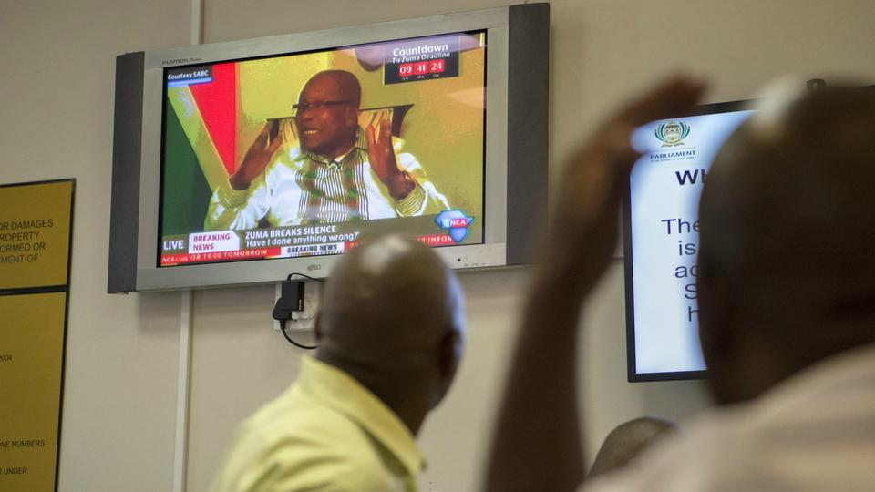 People at the Parliamentary Visitors Centre watch a television broadcast of South African president, Jacob Zuma, at the parliament on February 14, 2018, in Cape Town. South African President Jacob Zuma said ongoing efforts to unseat him by the ruling ANC party were unfair, adding that he had been given no reason by the party why he should resign.