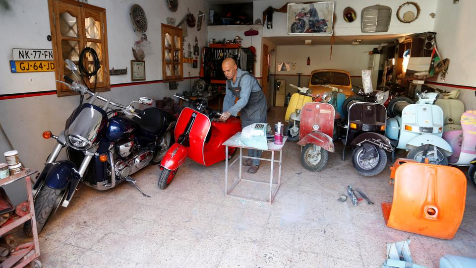 Libyan ex-military member Ibrahim al-Taweel seen at his workshop where he fixes classic cars and motorcycles.