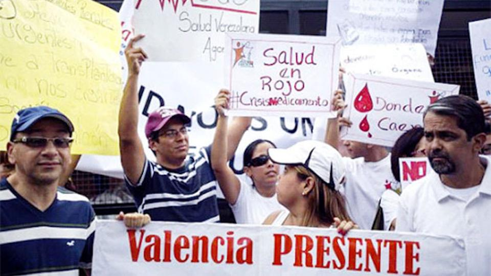 Protesters hold placards during a gathering in demand for medicines in Caracas, Venezuela on August 27, 2015