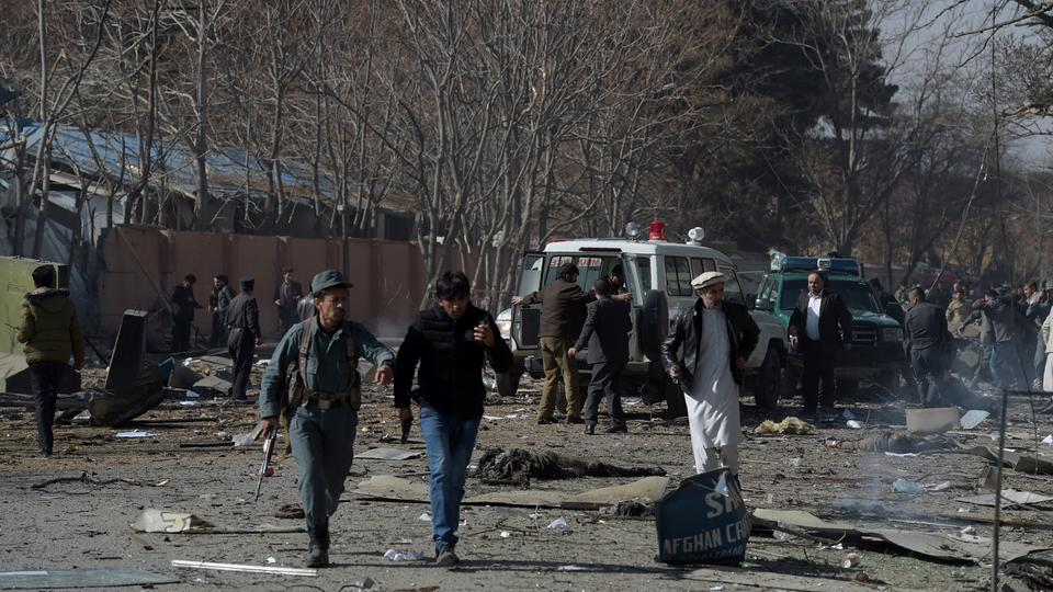 Afghan volunteers and policemen carrying injured men to an ambulance at the scene of a car bomb exploded in front of the old Ministry of Interior building in Kabul, on January 27, 2018.