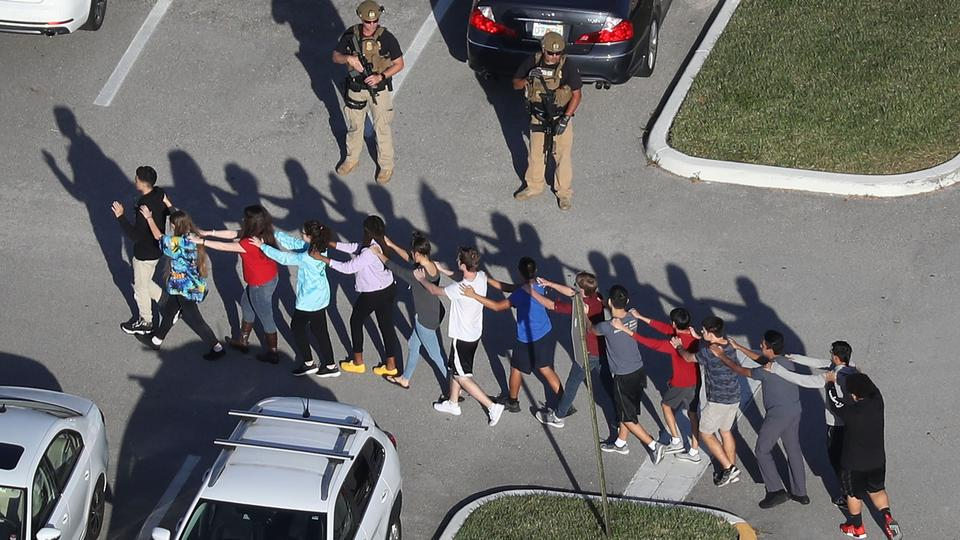 People are brought out of the Marjory Stoneman Douglas High School after a shooting at the school that killed at least 17 people.