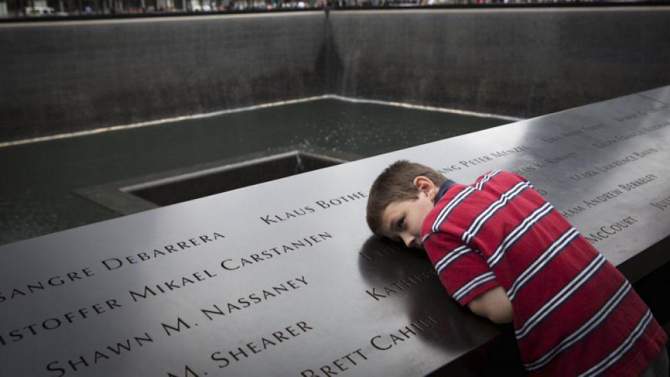 A child lays his head down on the 9/11 memorial during a ceremony.