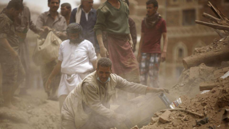 In this file photo, people search for survivors under the rubble of houses destroyed by Saudi airstrikes in the old city of Sanaa, Yemen.