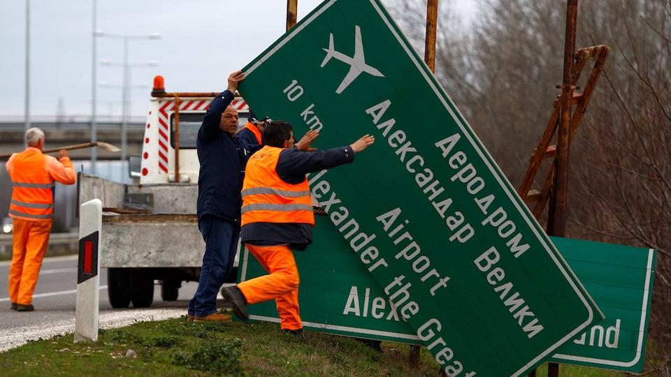 Workers dismantle a road sign with the name 'Alexander the Great Airport' in Skopje, Macedonia February 24, 2018.