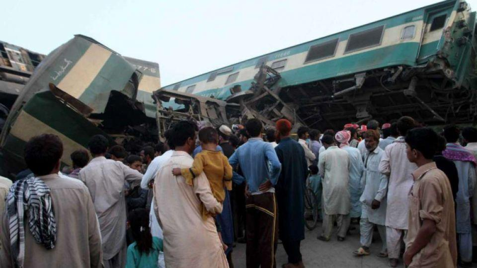 People look at a mangled passenger train that had collided with a freight train near Multan, Pakistan, Thursday, Sept. 15, 2016.
