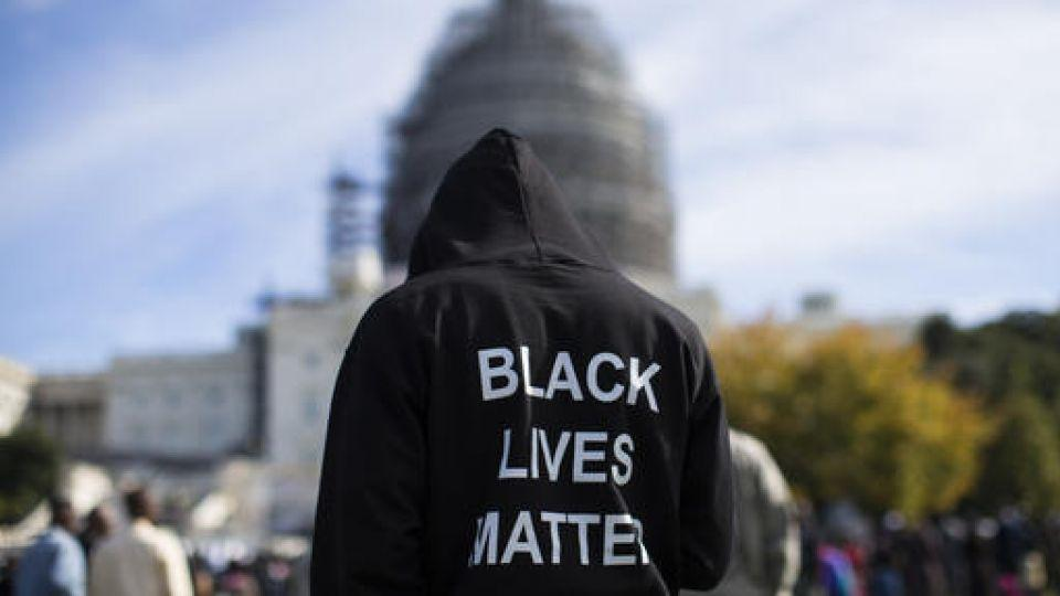 "In this 2015 file photo, a man wears a hoodie which reads, ""Black Lives Matter"" as he stands on the lawn of the Capitol building in Washington during a rally to mark the 20th anniversary of the Million Man March."