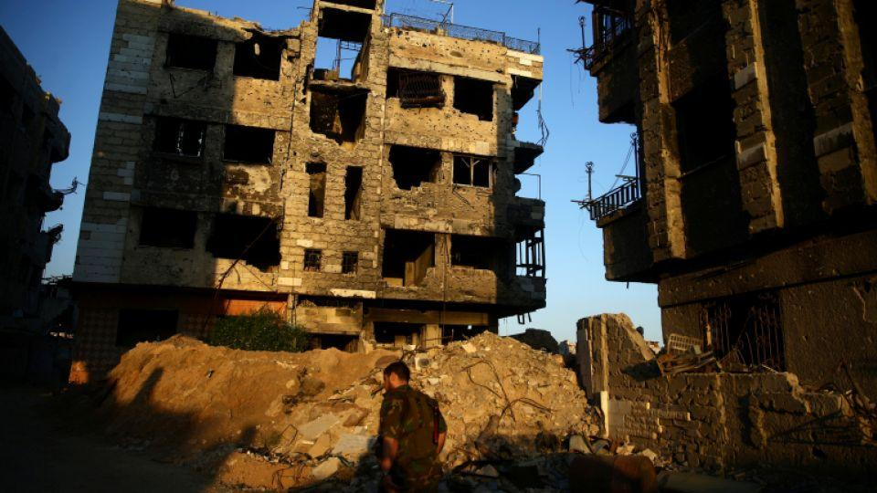 A fighter from the Free Syrian Army's Al Rahman legion walks past damaged buildings in the rebel held Jobar, a suburb of Damascus, Syria September 6, 2016.