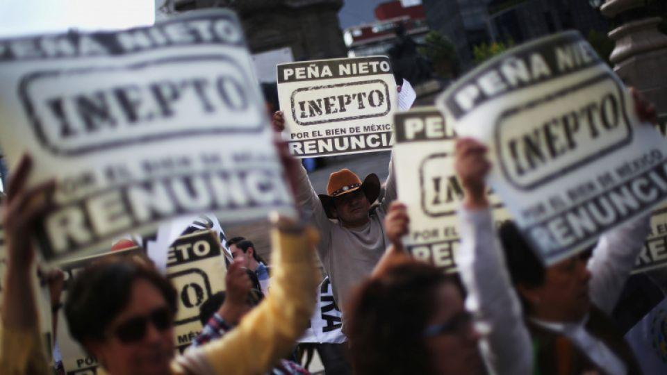 """Demonstrators hold signs as they take part during a march demanding the resignation of President Enrique Pena Nieto in downtown Mexico City, Mexico, September 15, 2016. The signs read, """"Pena Nieto, Inept. For the good of Mexico, resign."""""""