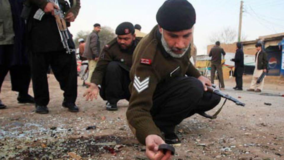 A security official examines a blast site in Pakistan's northwest.