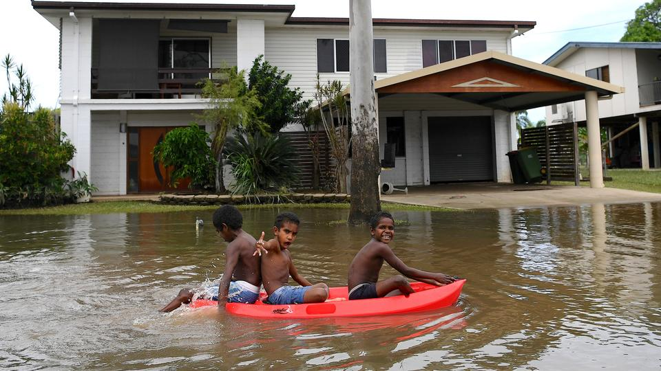Children float on a board past houses surrounded by flood waters in the town of Ingham, located in North Queensland, Australia, March 11, 2018.