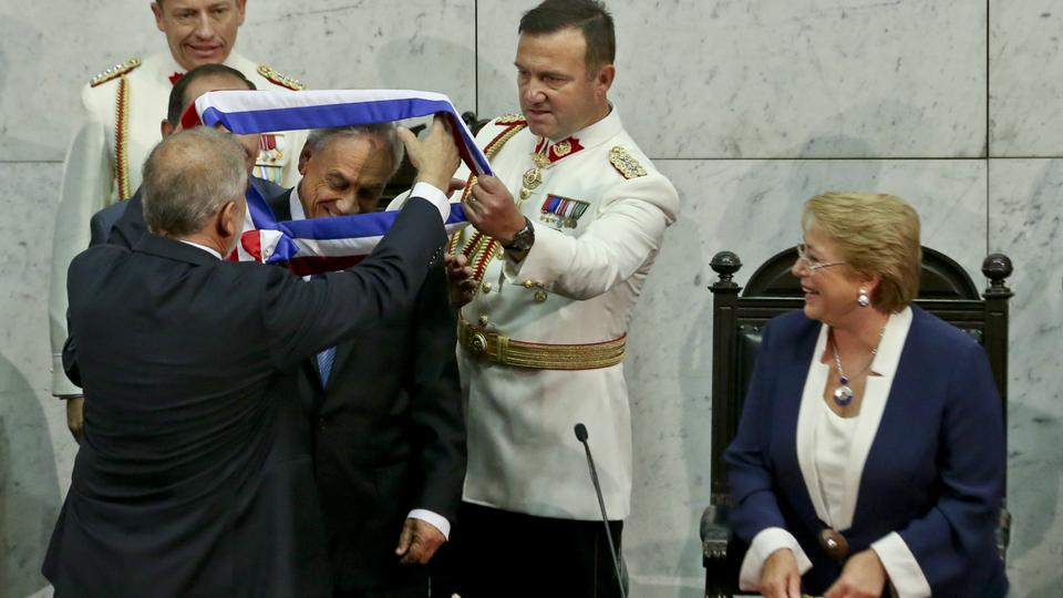 Chile's newly elected President Sebastian Pinera receives the presidential sash from Senate President Carlos Montes as Chile's outgoing President Michelle Bachelet looks on during his swearing-in ceremony at Congress in Valparaiso.