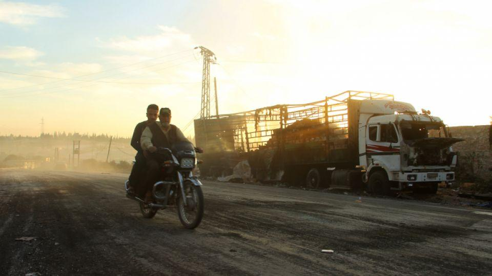 Men drive a motorcycle near a damaged aid truck after an air strike in Urm al-Kubra town, western Aleppo city, Syria September 20, 2016.