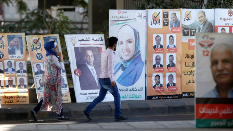 People walk past electoral posters for parliamentary candidates, ahead of the general elections to be held on September 20, in Amman, Jordan, September 16, 2016.