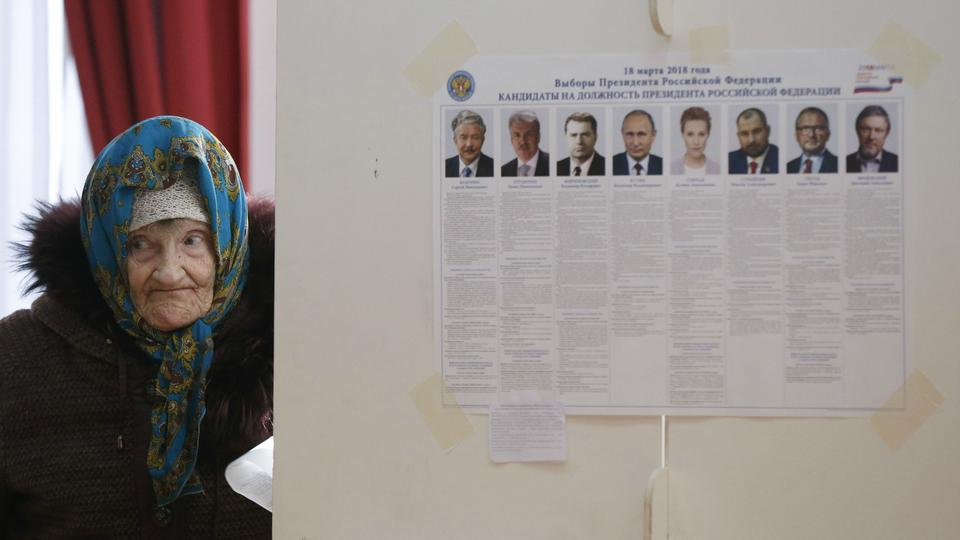 An elderly woman visits a polling station during the presidential election in Moscow.