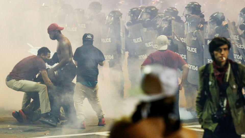 People maneuver amongst tear gas in uptown Charlotte, NC during a protest of the police shooting of Keith Scott, in Charlotte, North Carolina, U.S. September 21, 2016.
