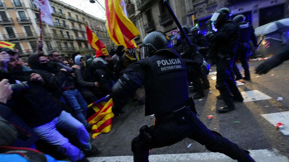 Protesters clash with riot police blocking the road leading to the central government offices during a demonstration in Barcelona on March 25, 2018 after Catalonia's former president was arrested by German police.