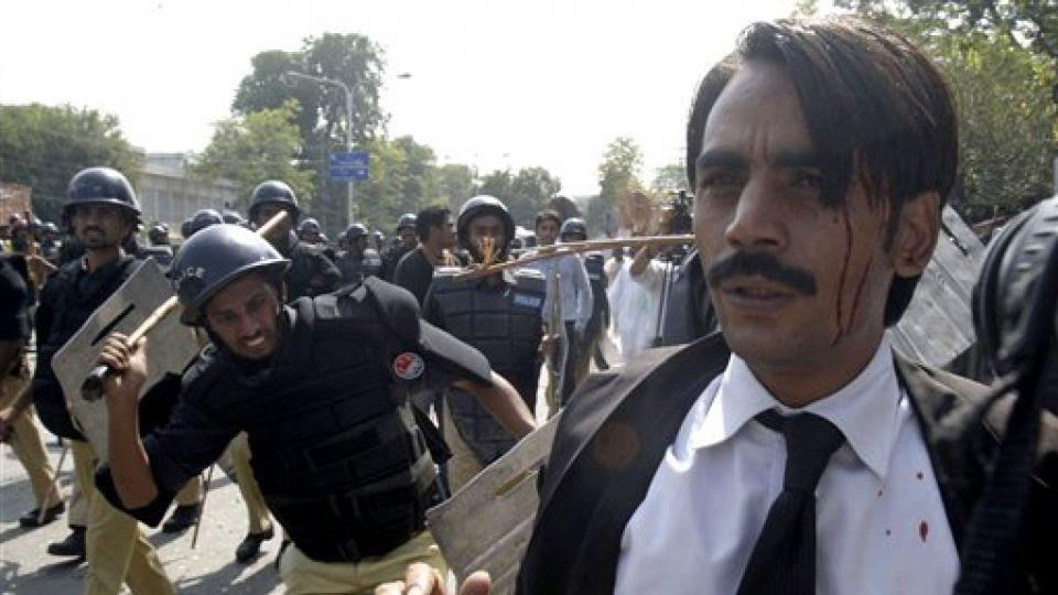 Pakistani police officers beat and arrest a lawyer after a clash between lawyers and police in Lahore, Pakistan on Oct. 1, 2010.