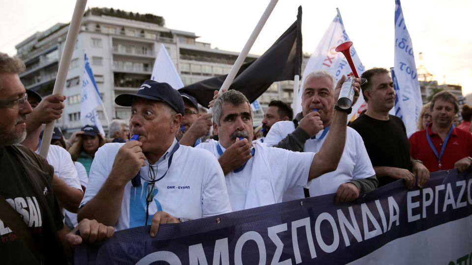 Protesters shout slogans and blow whistles during a demonstration in front of the parliament building, during a vote of an omnibus bill cutting spending on pensions, speed up privatizations and reform the electricity market, in Athens, Greece, Sept 27.