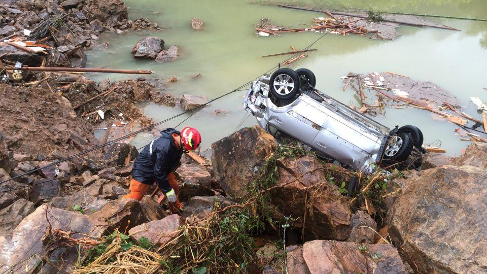 A rescue worker is seen next to an overturned car at the site of a landslide caused by heavy rains brought by Typhoon Megi, in Sucun Village, Lishui, Zhejiang province, China, September 29, 2016.