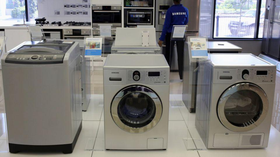 Samsung washing machines are seen as an employee inspects refrigerators at a Samsung display store in Johannesburg, October 3, 2013.