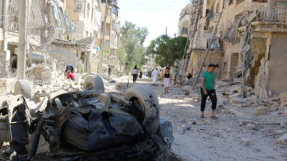 People inspect the damage at a site hit overnight by an air strike in the rebel-held area of Seif al-Dawla neighbourhood of Aleppo, Syria, September 30, 2016.
