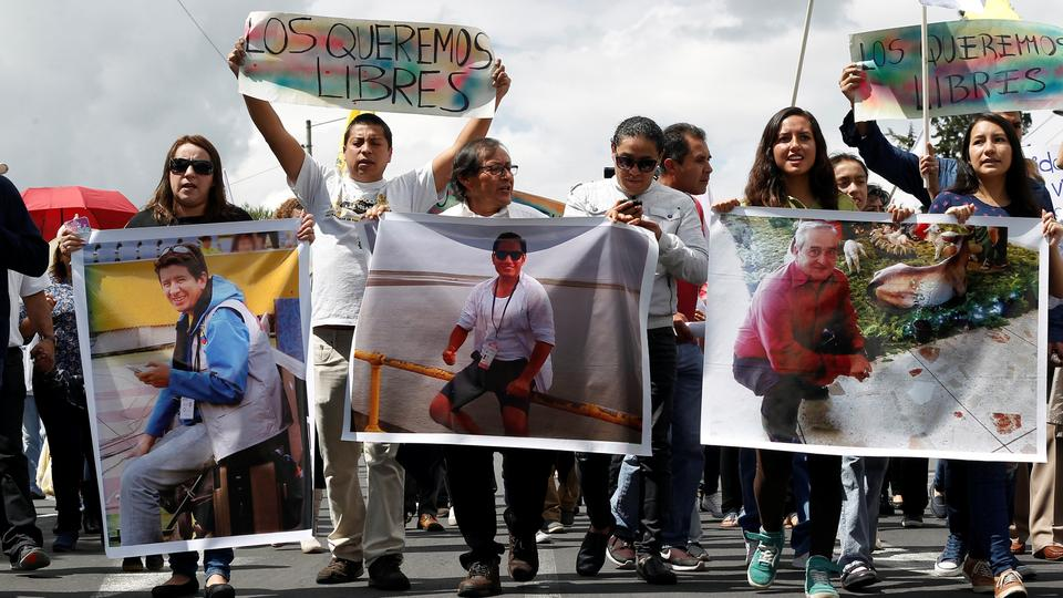 Relatives and friends hold pictures of Ecuadorean photojournalist Paul Rivas (L), journalist Javier Ortega (C) and their driver Efrain Segarra in Quito, Ecuador on April 1, 2018. The sign at the back reads: