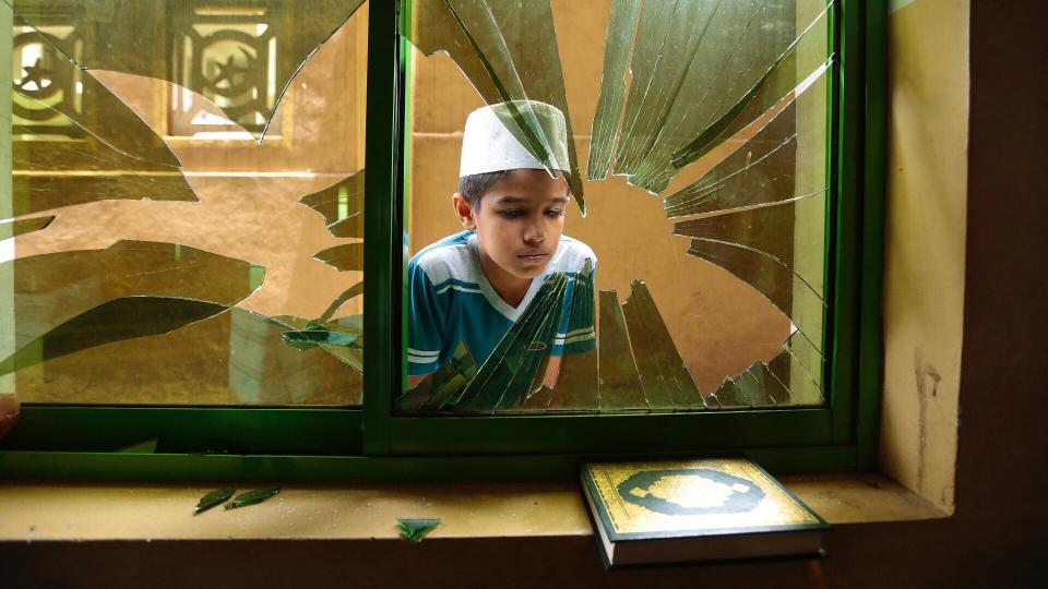 Ein srilankischer moslemischer Junge guckt durch ein zerbrochenes Fenster einer verwüsteten Moschee in Diana, Kandy, Sri Lanka, Freitag, den 9. März 2018. Am Freitag kehrte Ruhe in die gewaltbetroffenen muslimischen Viertel in Sri Lankas Region Kandy zurück Geschäfte, die als Verstärkung der Armee wiedereröffnet wurden, setzten buddhistischen Mobangriffen, die das Gebiet trafen, ein Ende.