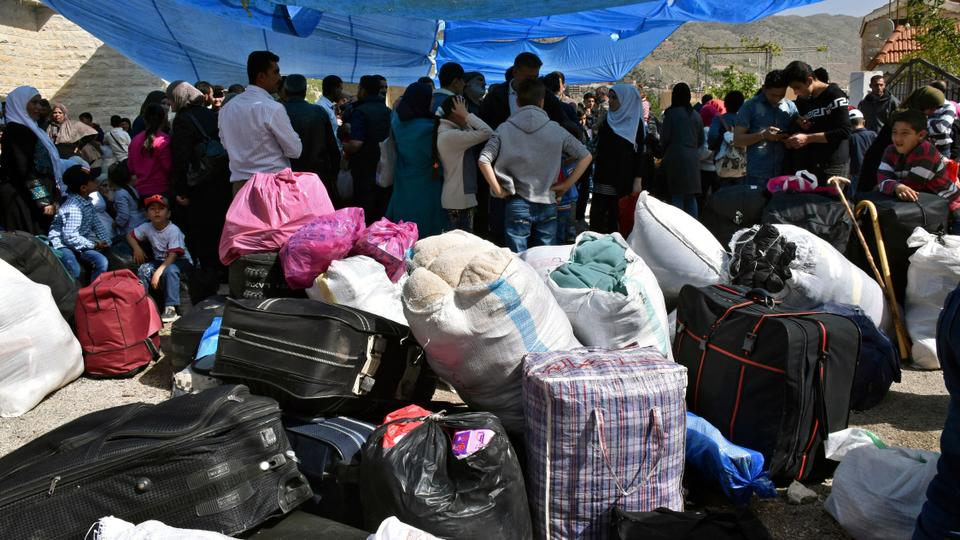 Displaced people who fled the Syrian war stand next to their belongings near the Lebanese-Syrian border as they prepare to return to their village of Beit Jinn in Syria, in the southern village of Shebaa, Lebanon, on April, 18, 2018.