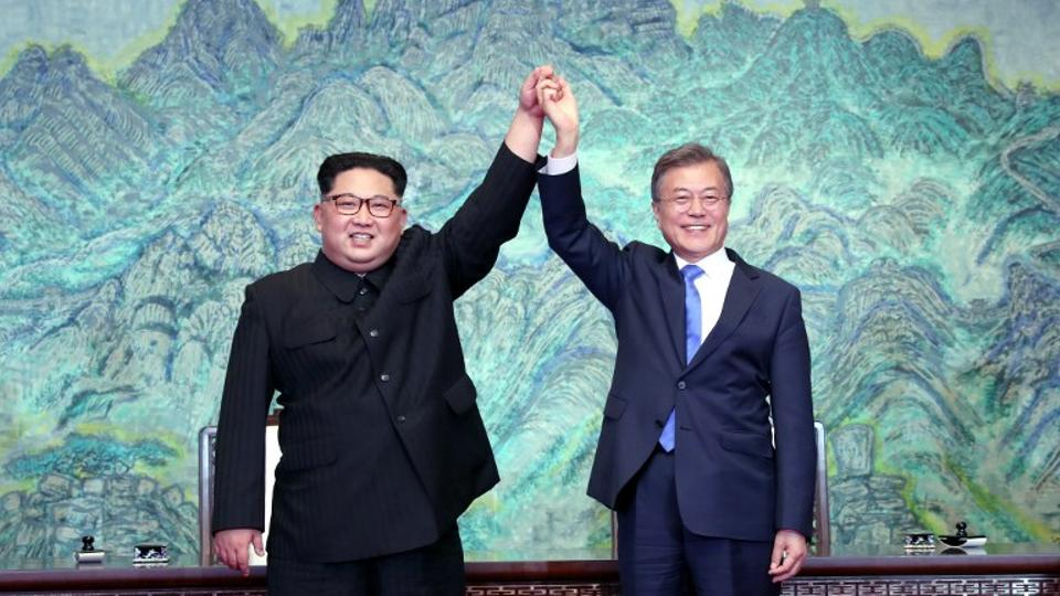 North Korea's leader Kim Jong-un (L) and South Korea's President Moon Jae-in (R) pose during a signing ceremony near the end of their historic summit at the truce village of Panmunjom on April 27, 2018.