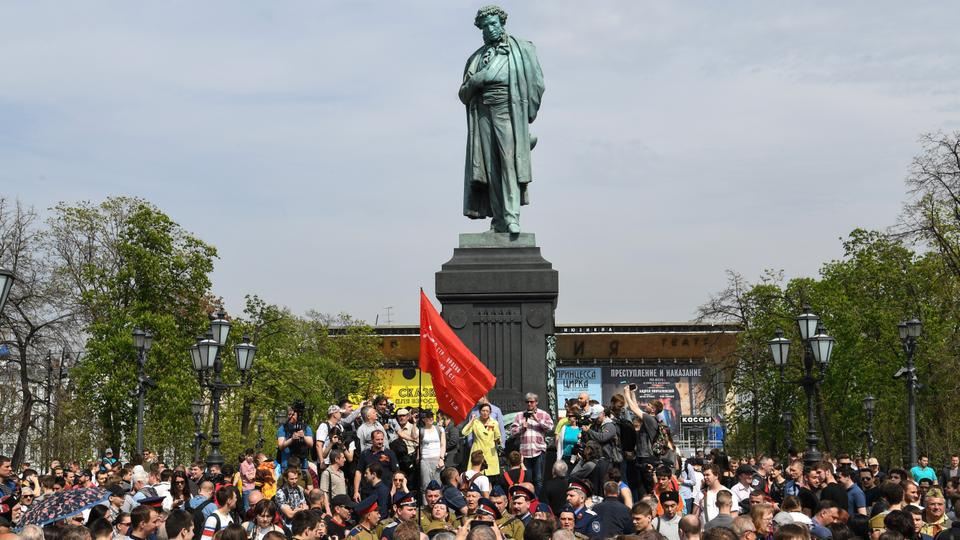 Pro-Kremlin activists gather around a monument of poet Alexander Pushkin some 30 minutes before the start of an unauthorized anti-Putin rally called by opposition leader Alexei Navalny on May 5, 2018