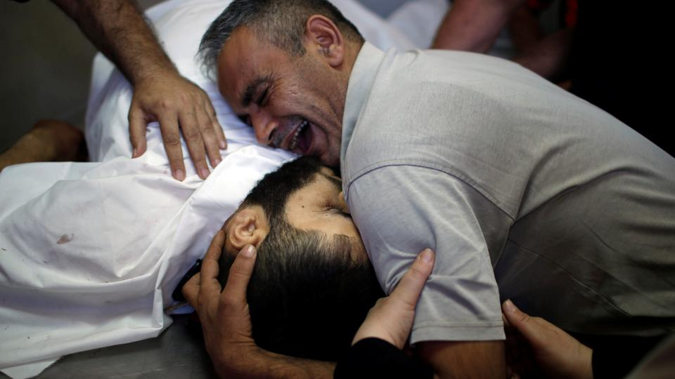 The brother of Palestinian Shaher al-Madhoon, who was killed during a protest at the Israel-Gaza border, reacts over his body at a hospital morgue in Gaza on May 14, 2018.