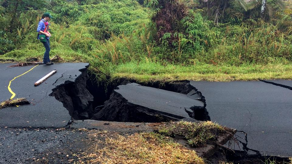 A Geologist Inspects Cracks On Road In Leilani Estates Following Eruption Of Kilauea Volcano