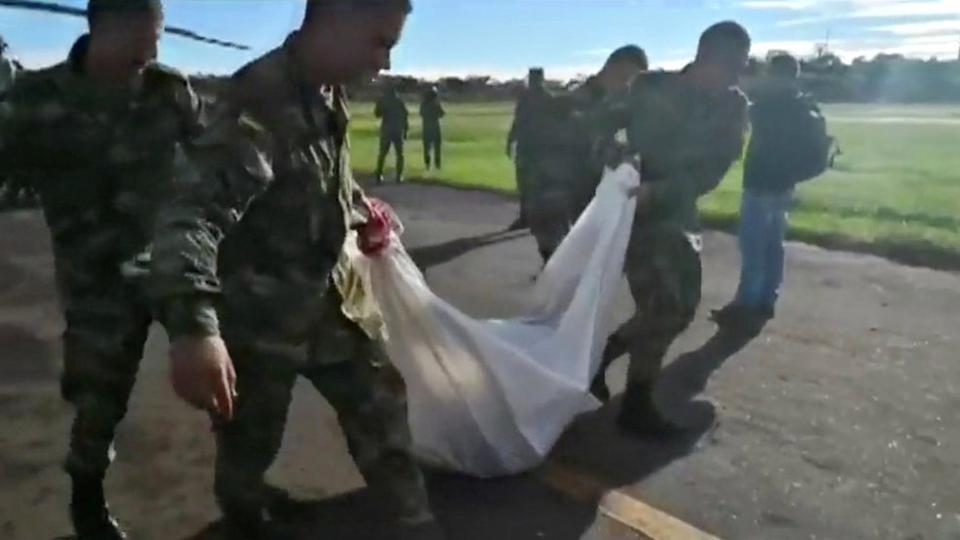 Army personnel carry a body bag after combat between the Colombian army and FARC dissidents, at a military base in Caqueta, Colombia in this still image taken from video, May 28, 2018.