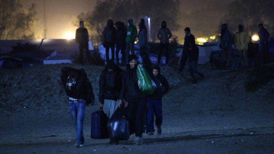 """Refugees leave the """"Jungle"""" migrant camp in Calais, northern France, on the eve of the camp's planned evacuation, October 23, 2016"""
