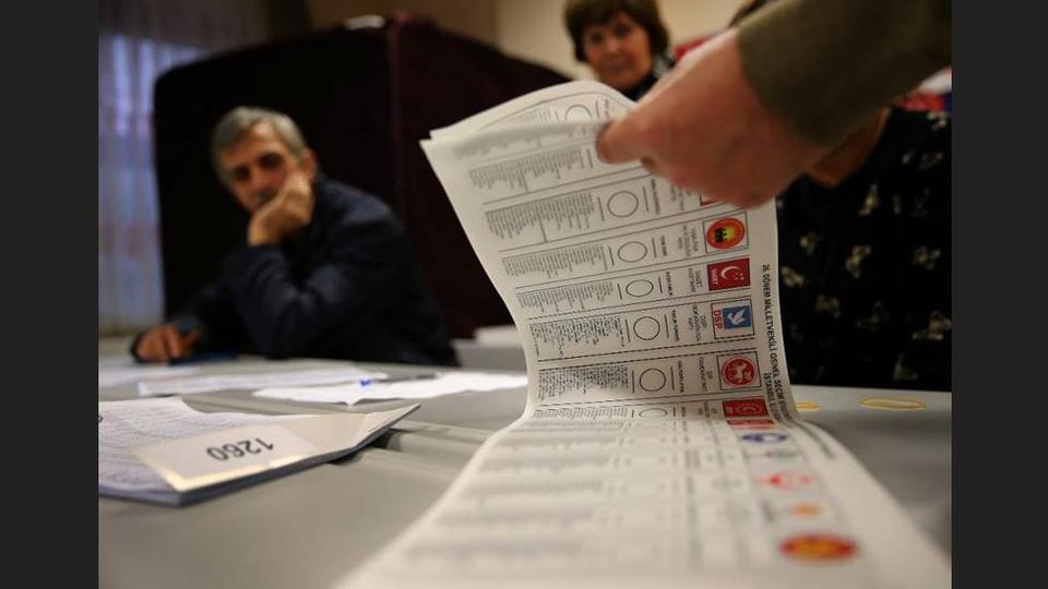 A Turkish election official counts ballots shortly after the polling stations closed at the end of election day, in Istanbul, Sunday, November 1, 2015.
