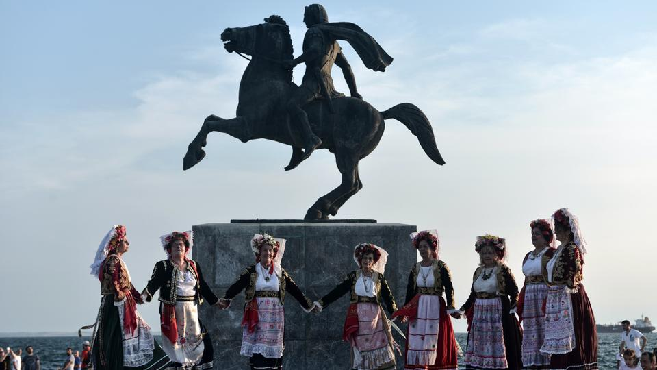 Dancers wearing traditional costumes perform in front of the statue of Alexander III of Macedon, commonly known as Alexander the Great, in Thessaloniki on June 12, 2018. Skopje and Athens resolved on June 12, 2018, a longstanding row after Macedonia's prime minister agreed to rename his country the Republic of North Macedonia, ending a 27-year dispute.