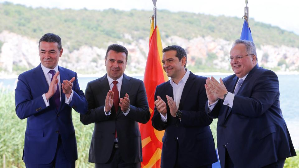 Greek Foreign Minister Nikos Kotzias, his Macedonian counterpart Nikola Dimitrov, Greek Prime Minister Alexis Tsipras and Macedonian Prime Minister Zoran Zaev applaud after signing an accord to settle a long dispute over the former Yugoslav republic's name as look on in the village of Psarades, in Prespes, Greece, June 17, 2018.