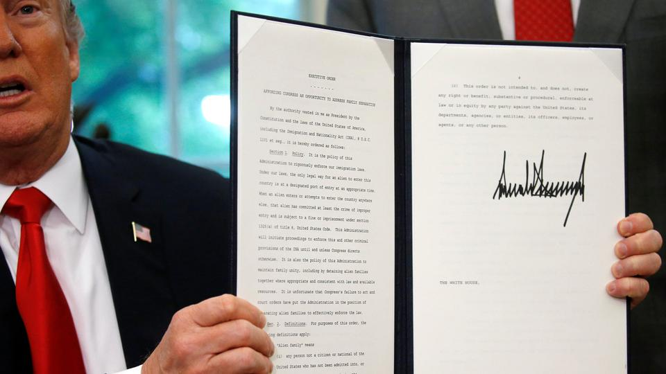 US President Donald Trump displays an executive order on immigration policy after signing it in the Oval Office at the White House in Washington, US, June 20, 2018.