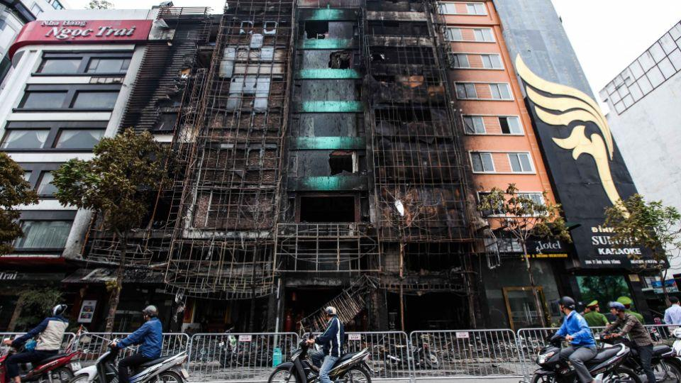 Motorists pass buildings damaged after a fire in a karaoke bar in Hanoi on November 2, 2016.