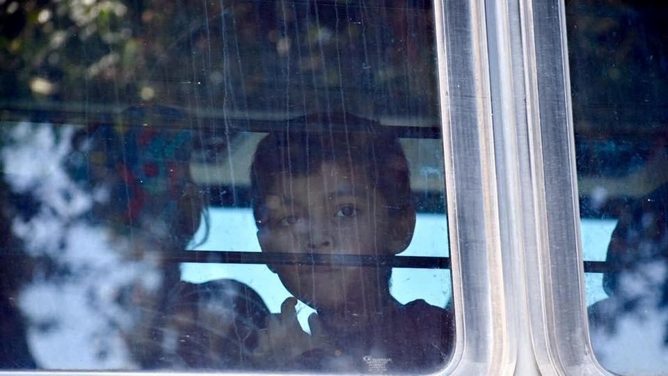 A child looks through the window of a bus carrying migrants near McAllen Detention Facility in McAllen, Texas, US on June 23, 2018, in this photo obtained from social media.
