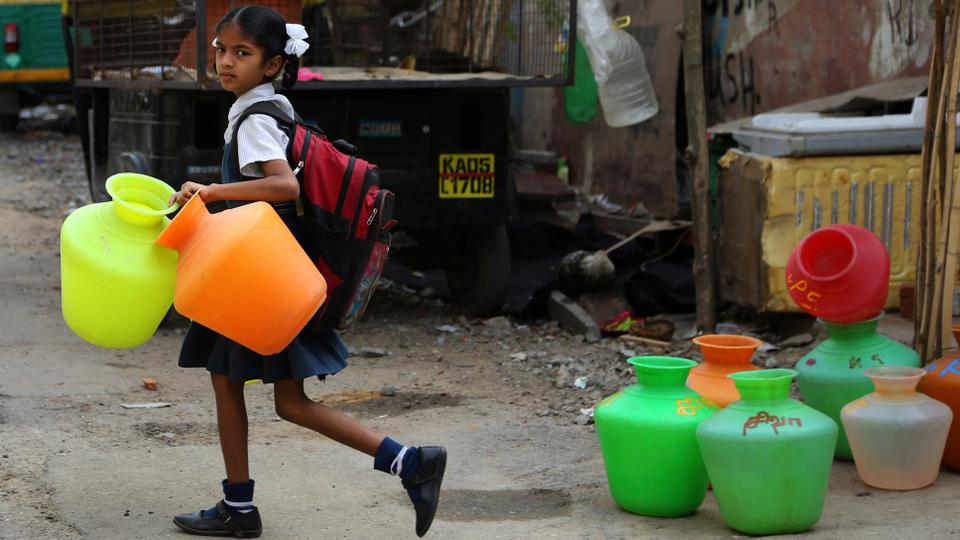 An Indian schoolgirl carries empty plastic vessels to fetch water from a shared tap before leaving for school, on World Water Day in Bangalore, India, March 22, 2018.